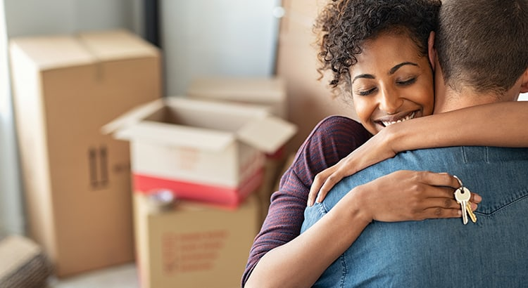 Young african woman holding home keys while hugging boyfriend in their new apartment after buying real estate. Lovely girl holding keys from new home and embracing man. Happy couple in their apartment around cardboard boxes.